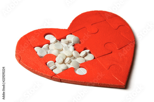 Heart puzzle red and white pills isolated on white background Canvas Print