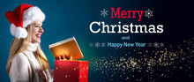 Merry Christmas And Happy New Year Message With Young Woman With Santa Hat Opening A Gift Box