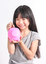 Portrait Of Little Asian Toddler Girl Putting Money Into Piggy Bank For Future Savings Isolated On White Background. Education Investing And Financial Concept