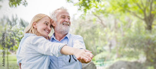 Obraz na plátně Happy old couple smiling dancing in a park on a sunny day, hoot senior couple relax in the forest spring summer time
