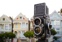 Twin-lens Reflex Camera On A Tripod In Front Of A Row Of Homes