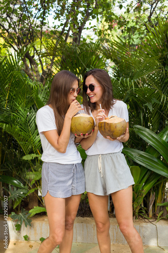 Two girls enjoy holiday with coconut juice in hand