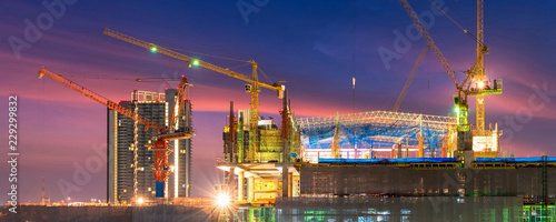 Fototapeta Construction site busy operate in beginning of building new complex infrastructure project at twilight time in panoramic banner cover size. obraz