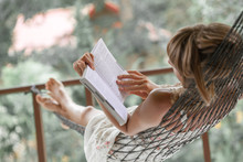 Woman In Summer Dress Lies In The Hammock In A Garden And Reads The Book