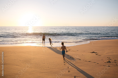 Energetic dad playing with kids on the beach at sunset - 229301046