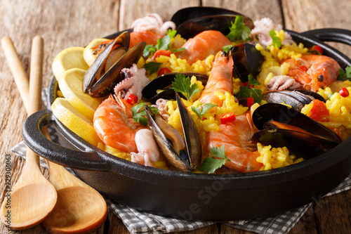 Paella seafood with king prawns, mussels, fish, and baby octopus served in a pan on a wooden table. horizontal