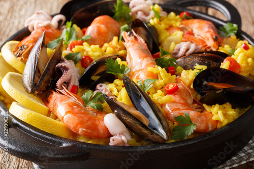 Spanish paella meal with seafood shrimp, mussels, fish, and baby octopus close-up in a pan on the table. horizontal, rustic