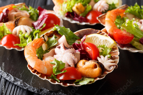 Healthy snack salad of seafood shrimp, baby octopus, mussels and scallops are served in seashells close-up. horizontal