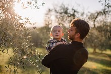 Father Holding His Son On Arms In Sunset Olive Garden