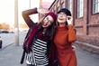 canvas print picture Outdoors fashion portrait young pretty best girls friends in friendly hug. Walking at the city. Posing at the street. Wearing stylish outerwear and hats. Bright make up. Positive emotions.