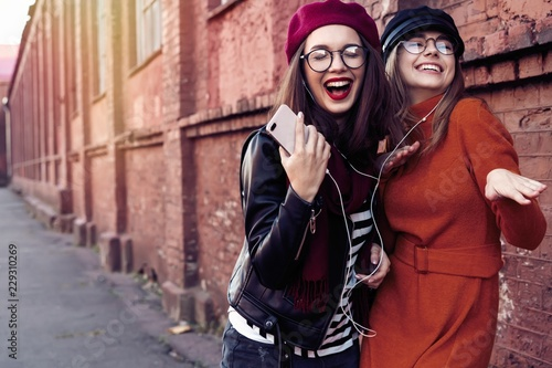 Foto  Two joyful young girls dancing while listening to music on smartphone, city outdoor