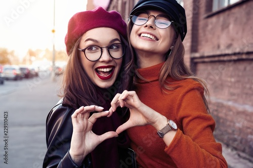 Fotografija Outdoors fashion portrait young pretty best girls friends in friendly hug