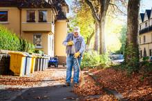 Senior Sweeping Autumn Leaves.