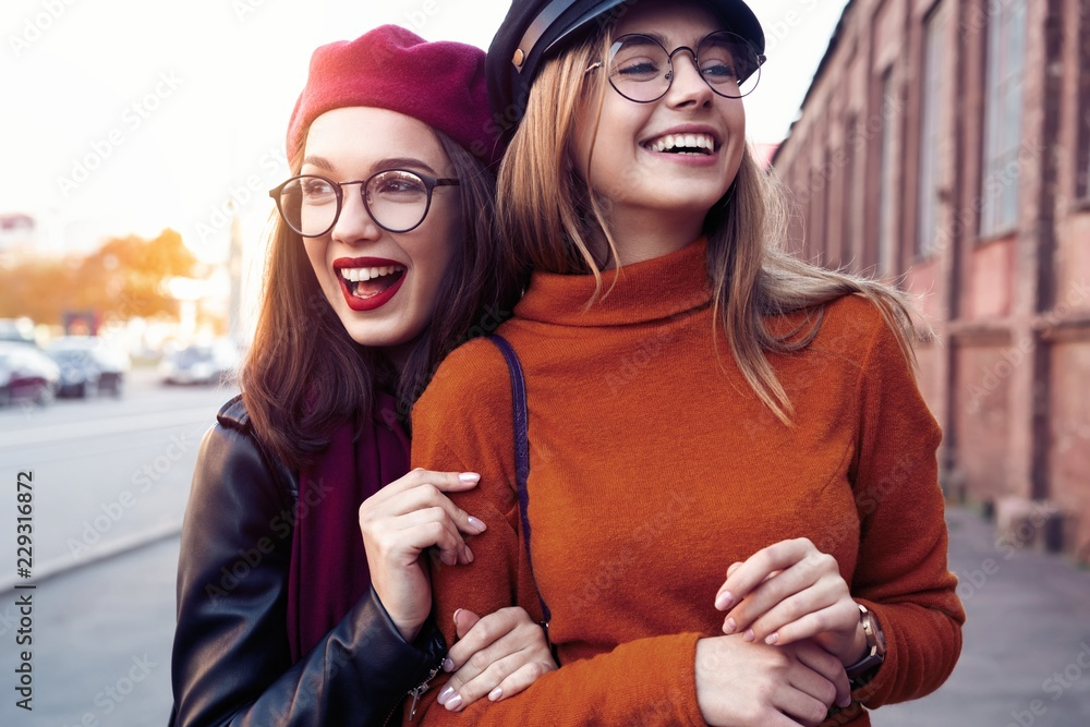 Fototapety, obrazy: Outdoors fashion portrait young pretty best girls friends in friendly hug. Walking at the city. Posing at the street. Wearing stylish outerwear and hats. Bright make up. Positive emotions.