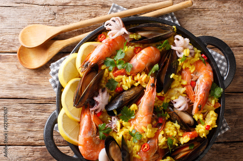 Spanish paella with shrimps, mussels, fish, and baby octopus close-up in a frying pan. horizontal top view