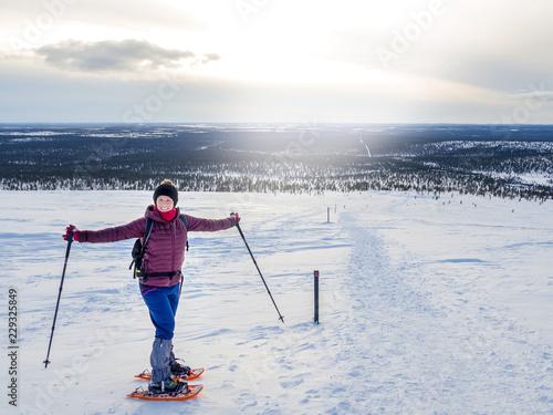 Photo  Pretty, young woman snowshoeing and enjoying splendid winter weather with abunda