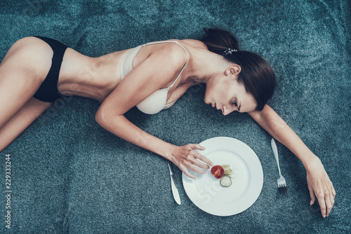 Photo Slim Girl with Anorexia Lying on Sofa with Plate.