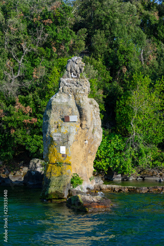 Fotografie, Obraz  Scultura di leone sulle scogliere dell'Isola Bisentina