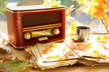 Old Open Book With Retro Radio And Autumn Leaves On Windowsill