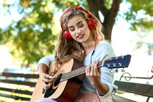 Beautiful Young Woman Listening To Music And Playing Guitar In Park