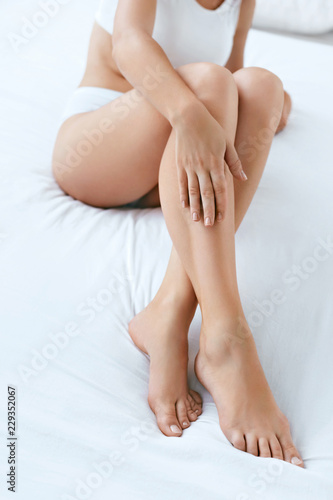 Fényképezés  Long Woman Legs With Smooth Soft Skin On White Bed Closeup