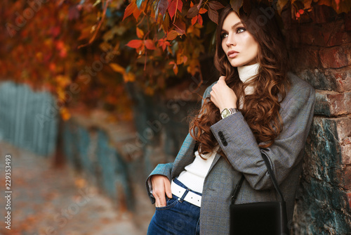Outdoor fashion portrait of young beautiful fashionable woman wearing white turtleneck, grey checked blazer, wrist watch, holding small leather bag, posing in autumn street Canvas Print