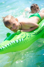 Older Brother Teenager Rolls Younger Brother Into The Sea On A Toy Inflatable Crocodile