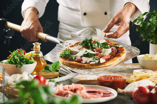Valokuvatapetti Chef preparing an Italian pizza on a paddle