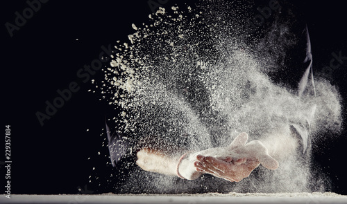 Flour spraying into air while man wipes his hands
