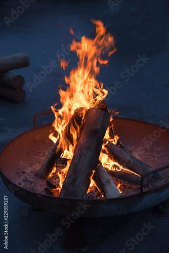 Feuerpfanne mit brennenden Holzscheiten Hochformat