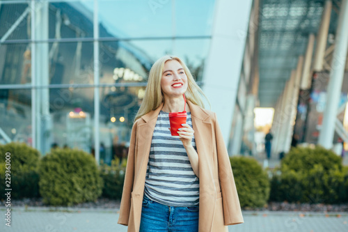 Elegant blonde business woman with red lips in beige coat enjoying coffee to go while walking outdoor over business center Wallpaper Mural