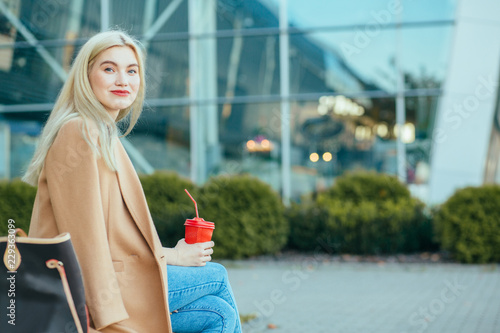 Photo  Side view portrait of blond dreamy elegant business woman red lips in beige coat with coffee to go during a break sitting outdoors at financial district with modern building on background