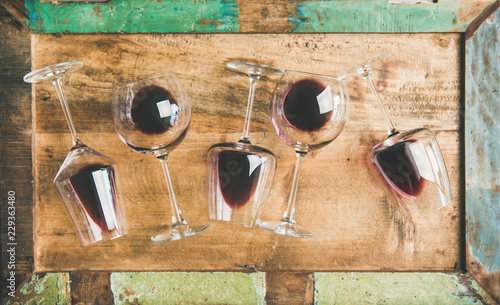 Obraz na płótnie Flat-lay of red wine in glasses over rustic wooden tray background, top view