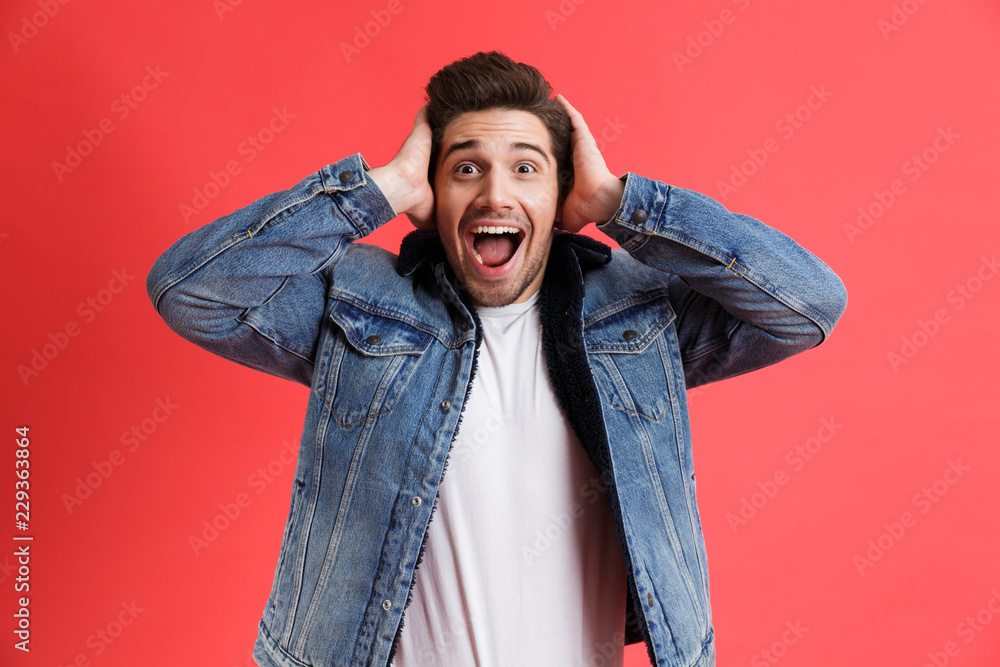Fototapeta Portrait of an excited young man dressed in denim jacket