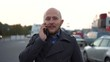 Handsome bald-headed man with beard talking on cellphone. Blury steady shot