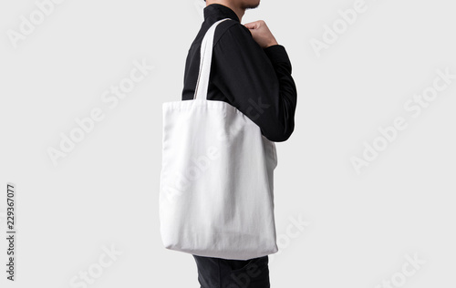 Man is holding bag canvas fabric for mockup blank template isolated on gray background Canvas Print