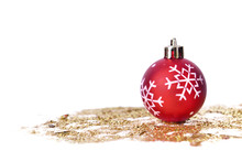 Red Christmas Bauble On Golden Glitters Isolated On White Background