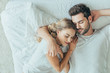 canvas print picture - top view of beautiful young couple sleeping together and hugging in bed at home
