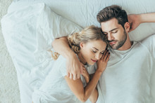 Top View Of Beautiful Young Couple Sleeping Together And Hugging In Bed At Home