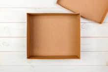Opened Empty Cardboard Box On Wooden Background. Top View