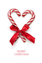 Two Red Striped Candy Cane In Heart Shape With Red Bow And Merry Christmas Text Isolated On White Background. Vector Christmas Design Element.
