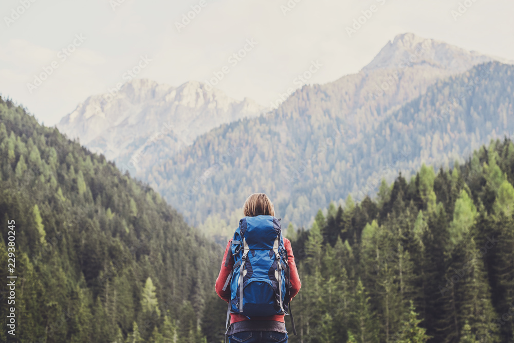 Fototapeta Young woman traveler in Alps mountains. Travel and active lifestyle concept