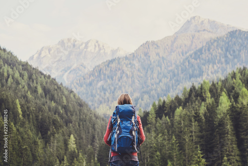 Young woman traveler in Alps mountains. Travel and active lifestyle concept