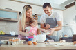 A happy family prepares baking in the kitchen.