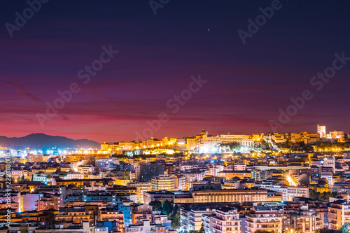 Photo Stands Crimson Cagliari at night, capital of the region of Sardinia, Italy. Beautiful skyline image of the big city on the island.
