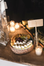 Cocktail Cheese And Grapes Appetizers In Decorated Table At Night With Candles