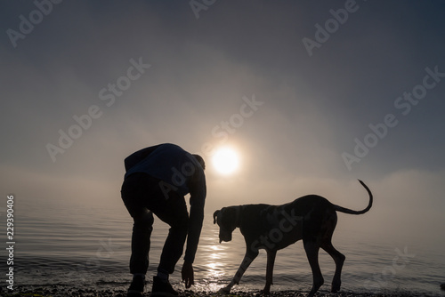 Photo Stands Cappuccino Silhouetted man and dog at the beach in heavy fog searching the rocks.