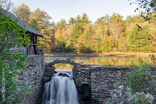 Fototapeta Stone wall and building with waterfall and Autumn trees reflected on Lake in upstate New York