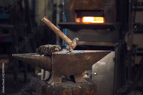 Fotografia Mallet and gloves on an anvil in front of a furnace