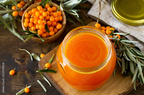 Fresh Sea Buckthorn Berries and Fruit Syrup Sea Buckthorn on a wooden rustic background. Copy space.